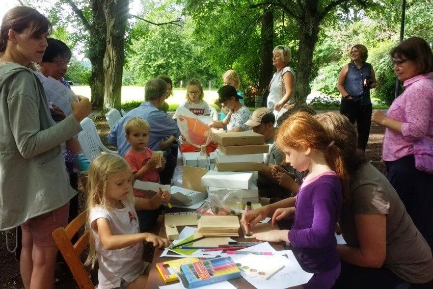 Kinder und Erwachsene basteln im Freien während der Sommefreizeit auf Schloss Craheim