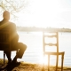 sitzender Mann alleine blickt auf den See, neben ihm ein leerer Stuhl