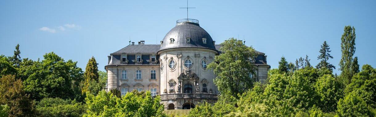 Schloss Craheim von Ferne mit Kreuz auf dem Schlossdach der Kuppel