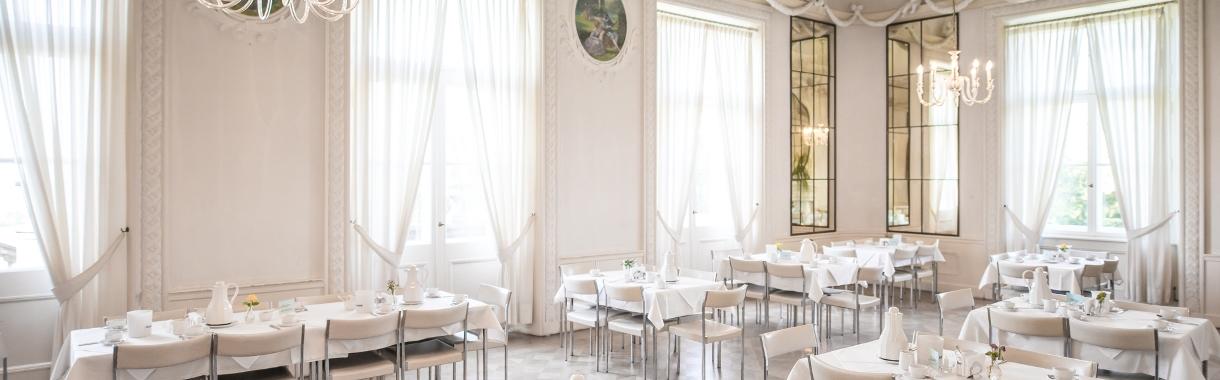 Spiegelsaal mit gedeckten Tischen und großen Fenstern