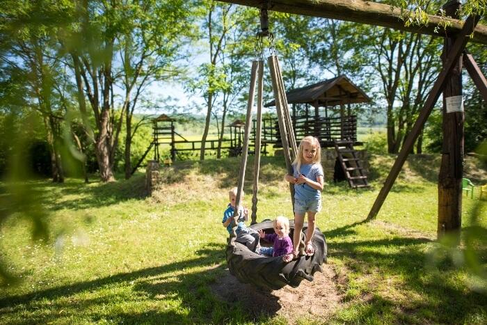 Der Spielplatz neben dem Gästehaus für Kinder mit Reifenschaukel und Kletterburg