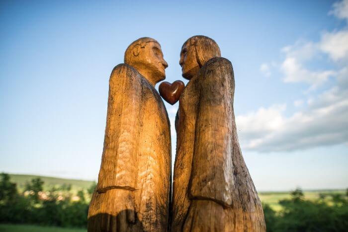 Ein Liebespaar steht sich gegenüber und trägt in der Mitte ein Herz
