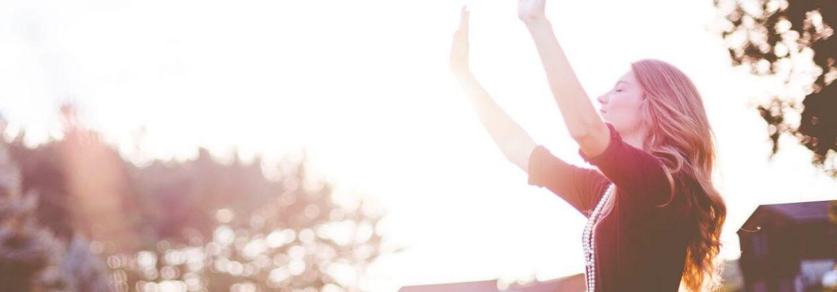 Frau im Gebet hebt die Hände zum Lobpreis