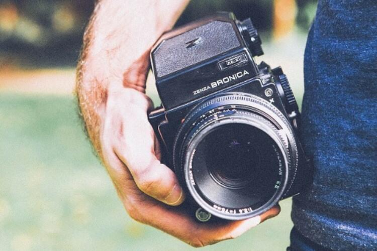 Fotoapparat in der Hand eines Teilnehmenden des Foto Seminars