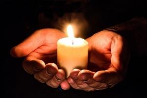 Mann hält brennende Kerze in Händen