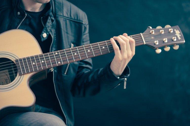 Mann spielt Gitarre und macht Lobpreis