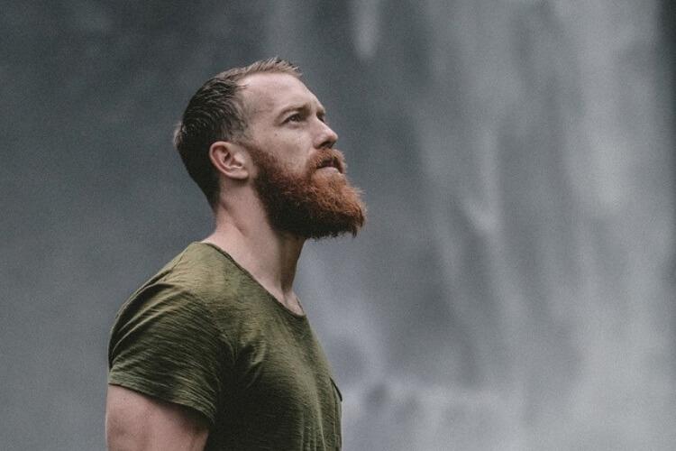 Mann unter Wasserfall
