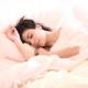 Frau liegt im Bett und träumt