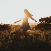 Frau geht über eine Wiese und fühlt sich lebendig